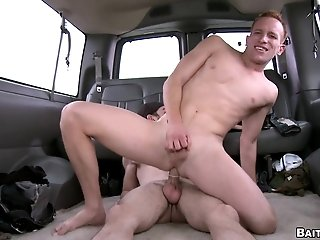 Tattooed twink drills a dude's asshole from behind in a minivan